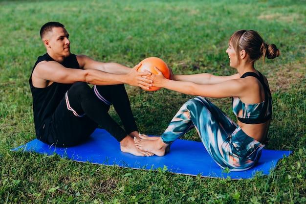 Homem mulher, junto, fazendo, exercício, com, um, bola, ao ar livre