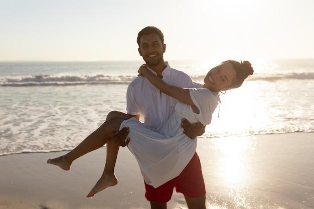 Homem, mulher levando, em, seu, braços, praia