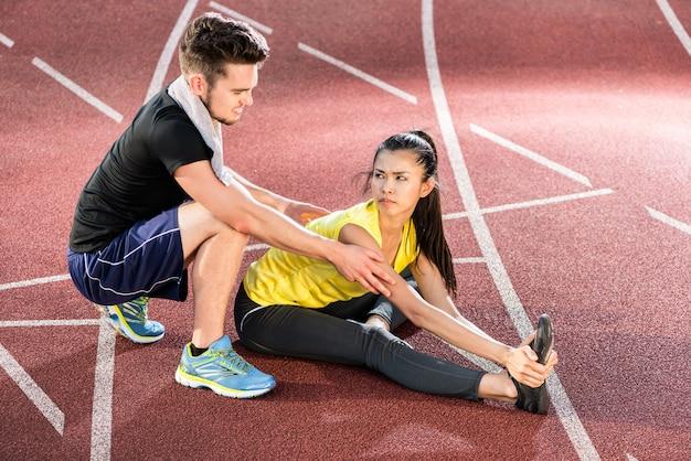 Homem mulher, ligado, cinza, pista, de, arena esportiva, esticar, exercícios