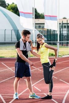 Homem mulher, ligado, concreto cinza, pista, de, arena esportiva, esticar, exercis