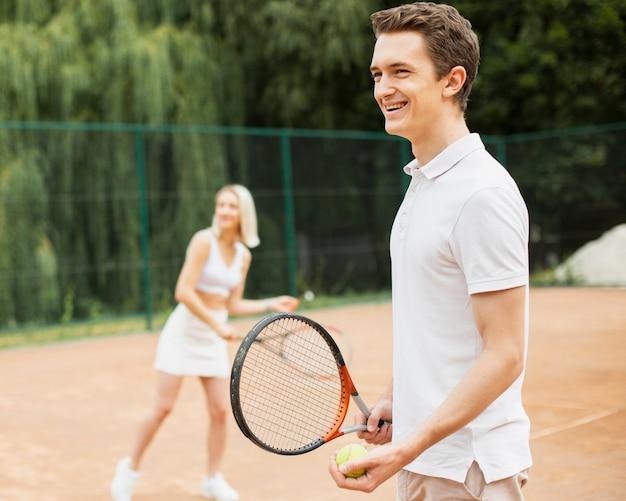 Homem mulher praticando tênis
