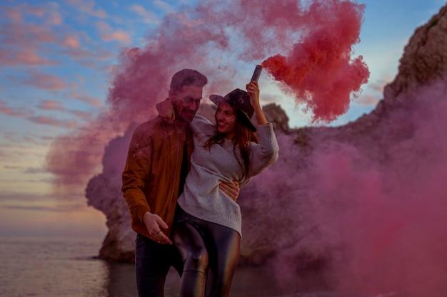 Homem, mulher segura, com, cor-de-rosa, bomba fumaça, ligado, costa mar