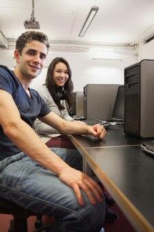 Homem mulher, sentando, em, computador, escrivaninha