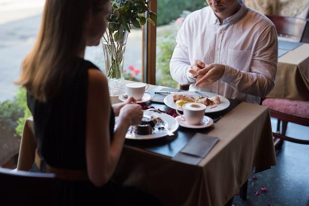 Homem mulher, sentando tabela, com, desserts, e, bebidas, em, café