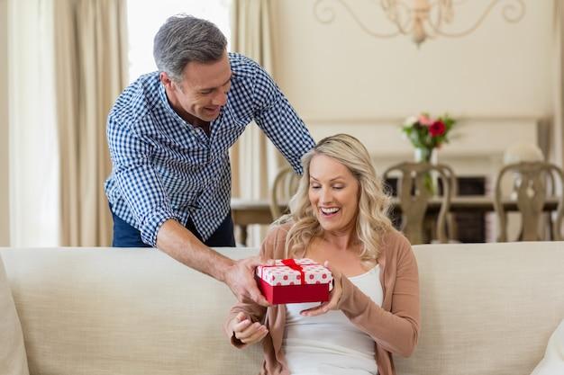 Homem mulher surpreendente com um presente na sala de estar