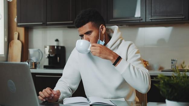 Homem multirracial com máscara médica falando pelo smartphone e trabalhando no computador em casa cozinha