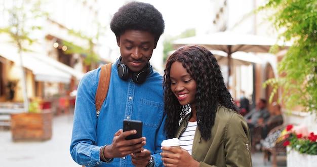 Homem multirracial elegante e sua namorada usando seu smartphone enquanto caminhava pela rua ...