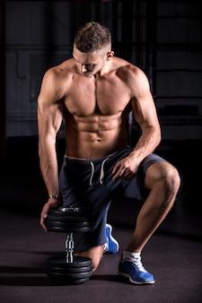 Homem muscular olhando haltere