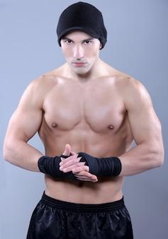 Homem muscular que dobra seu bíceps - tiro do estúdio.