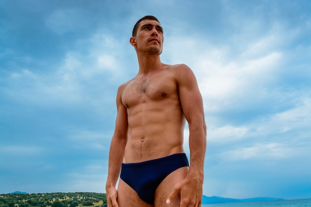 Homem muscular que está na praia em um speedo.