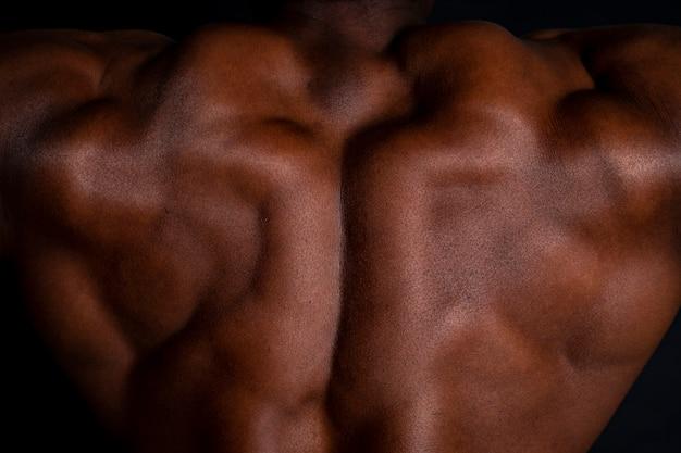 Homem musculoso africano de volta com fundo preto