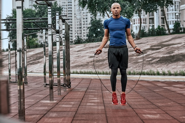 Homem musculoso africano está pulando corda. retrato de jovem musculoso se exercitando