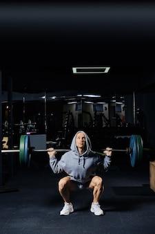 Homem musculoso agachamento com barra no ginásio
