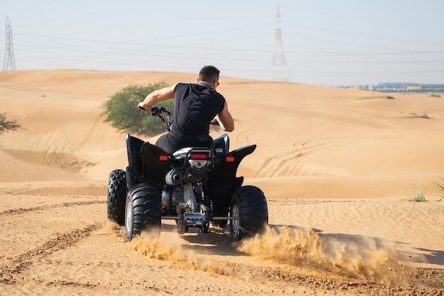 Homem musculoso andando de quadriciclo no deserto