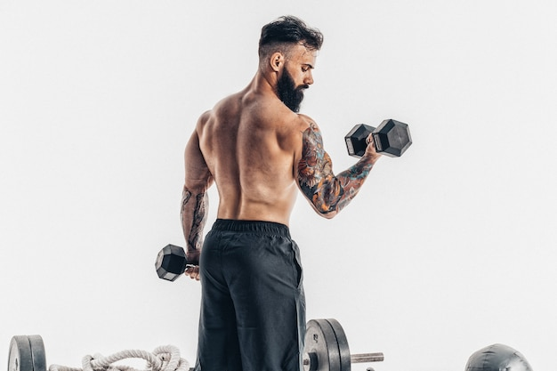 Homem musculoso atleta fisiculturista com um treino de torso nu com halteres.