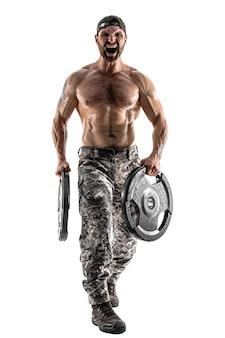Homem musculoso atleta fisiculturista em calças camufladas com um treino de torso nu com halteres em uma parede branca. isolar