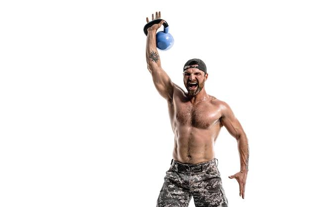 Homem musculoso atleta fisiculturista em calças camufladas com um treino de torso nu com kettlebell em uma parede branca. isolar