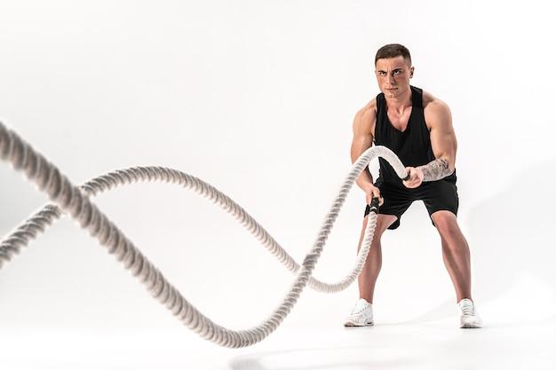Homem musculoso atraente malhando com cordas pesadas. foto de homem bonito em roupas esportivas, isolada na parede branca. crossfit