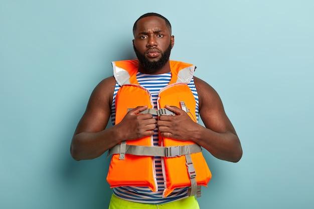 Homem musculoso barbudo sério e confiante posando com itens de praia