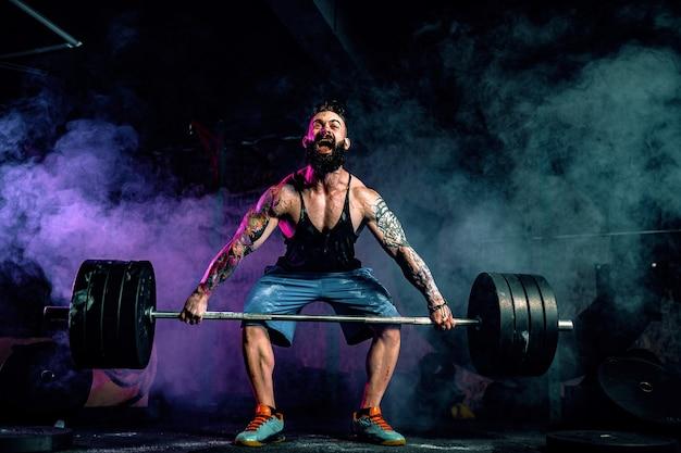 Homem musculoso barbudo tatuado fitness fazendo deadlift uma barra sobre a cabeça no moderno centro de fitness.