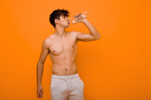 Homem musculoso bebendo água de garrafa