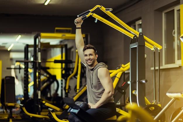 Homem musculoso bonito malhando na academia