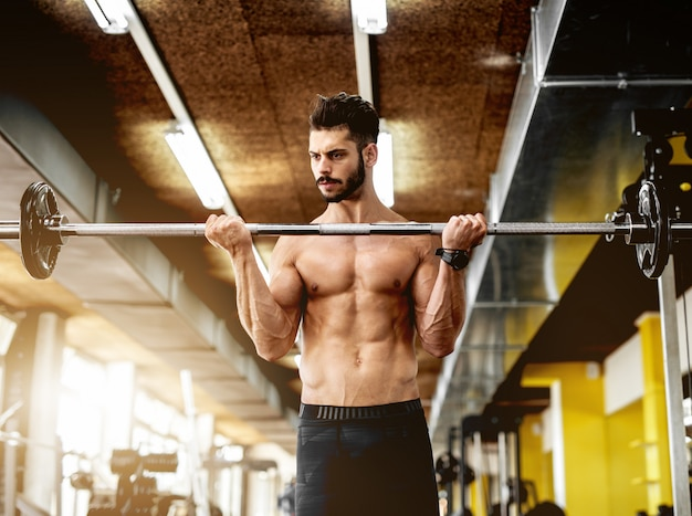 Homem musculoso bonito malhando na academia.