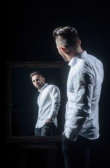Homem musculoso bonito ou atleta cara com corpo sexy de fisiculturista tem barba na cara séria em calças, camisa branca perto de espelho vintage isolado no fundo preto
