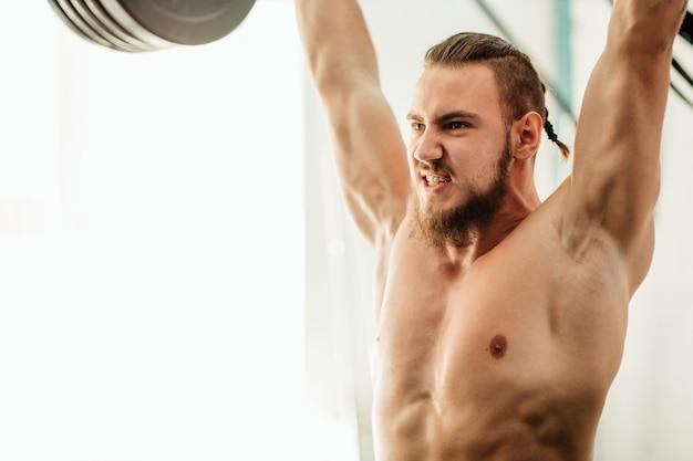 Homem musculoso brutal com trem de barba com barra levantada sobre a cabeça no ginásio
