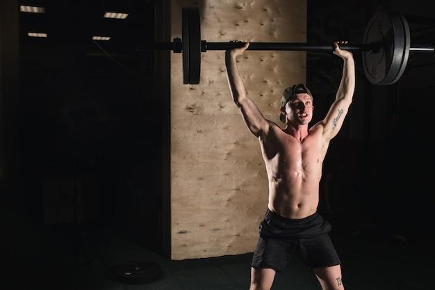 Homem musculoso com barba treinar com barra levantada sobre a cabeça no ginásio
