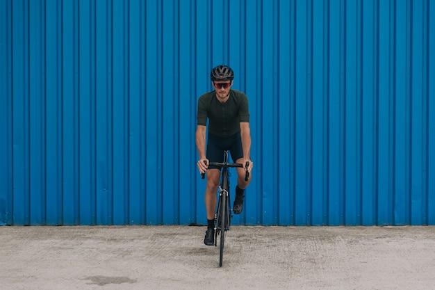 Homem musculoso com capacete de segurança e óculos espelhados, andar de bicicleta ao ar livre. ciclista caucasiana com treinamento ativo em áreas urbanas. parede azul em fundo.