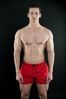 Homem musculoso com corpo forte. esporte e preparação física. atleta ou desportista de calção vermelho. homem de aptidão exercitando no ginásio. ajustar seu corpo e perder peso. atleta aquecendo antes do treino. seja forte.