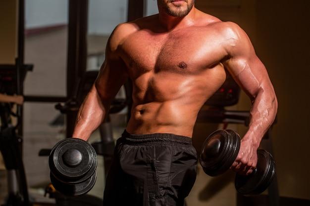 Homem musculoso com halteres. fisiculturista forte na academia. homem malhando com halteres. atleta no ginásio treinando com halteres. abs e bíceps. homem musculoso no fundo do ginásio com halteres.