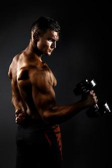 Homem musculoso com halteres. vista lateral. fundo preto