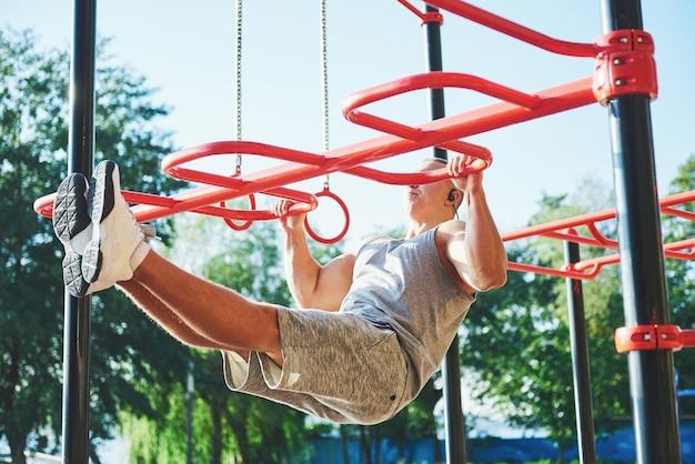 Homem musculoso com lindo torso se exercitando nas barras horizontais