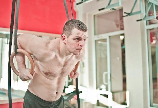 Homem musculoso com torso nu fazendo exercício nos anéis de ginástica no ginásio