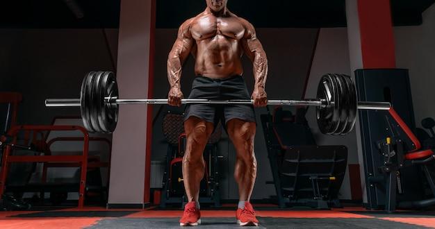 Homem musculoso com uma barra nas mãos. deadlift. conceito de musculação. mídia mista