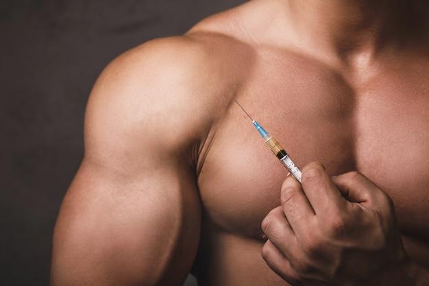 Homem musculoso com uma seringa na mão. conceito de treino de força e uso de esteróides anabolizantes.
