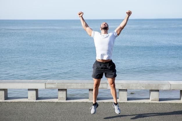 Homem musculoso comemorando sucesso esportivo no mar