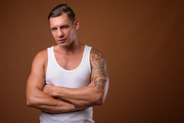 Homem musculoso contra parede marrom