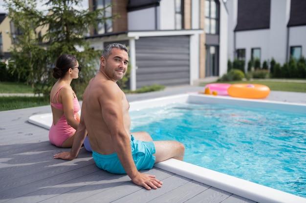 Homem musculoso de cabelos grisalhos. homem musculoso e grisalho sentado perto da filha e da esposa, descansando perto da piscina