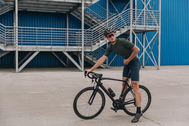 Homem musculoso descansando em uma bicicleta após pedalar em área urbana