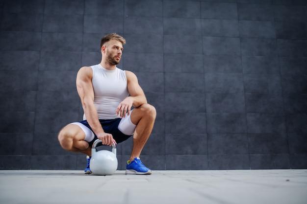 Homem musculoso desportivo caucasiano posando, agachado e segurando o sino de chaleira ao ar livre.