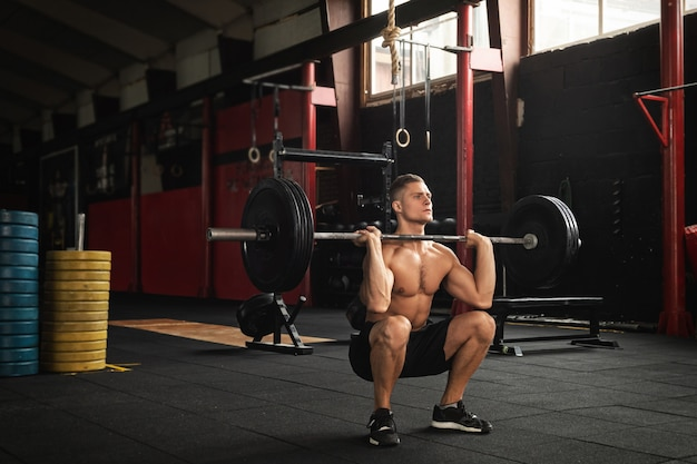 Homem musculoso durante o treino de levantamento de peso no ginásio