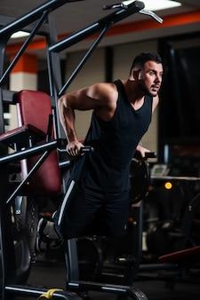 Homem musculoso durante um treino na academia treina o tríceps nas barras paralelas