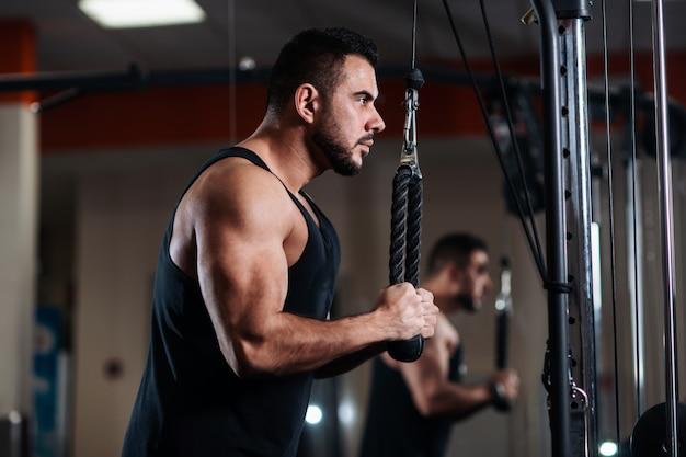 Homem musculoso durante um treino no ginásio treina o tríceps