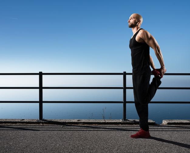 Homem musculoso e atlético em pose de alongamento perto do mar