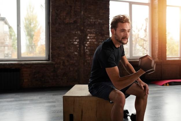 Homem musculoso e atlético treinando bíceps na academia