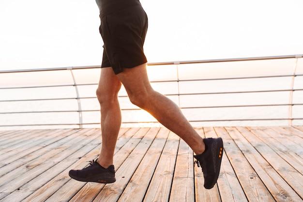 Homem musculoso e desportivo de bermuda e camiseta correndo ao longo do cais ou calçadão à beira-mar, na manhã