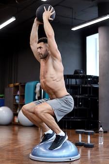 Homem musculoso e em forma, exercitando-se com a bola de medicina na bola de bosu do hemisfério de ginástica no ginásio.